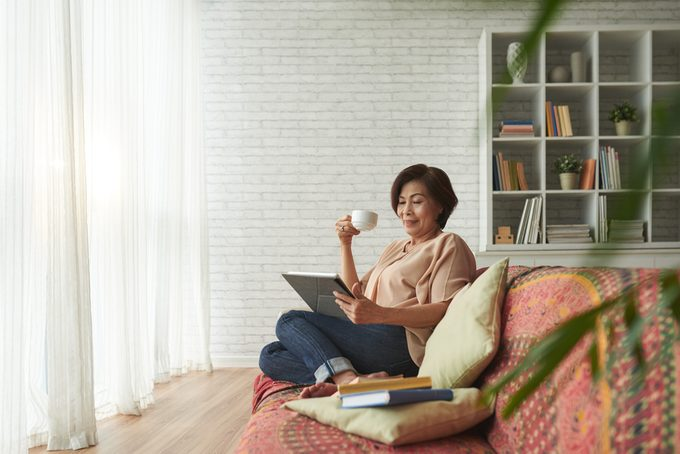 Vietnamese senior woman drinking tea and reading book on tablet computer