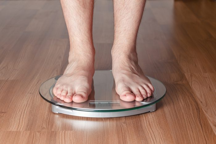 man's feet on a scale