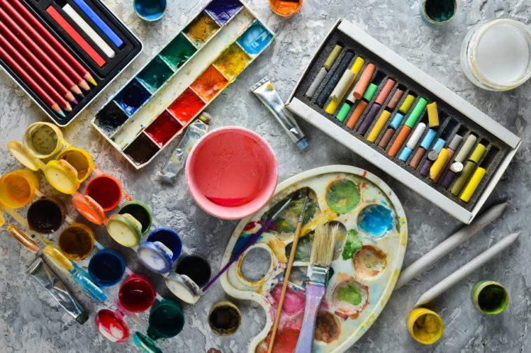 Artistic tools for drawing paintings on a gray concrete background. Palette, gouache, oil paint, brushes, colored crayons, pastel, colored pencils. Top view.