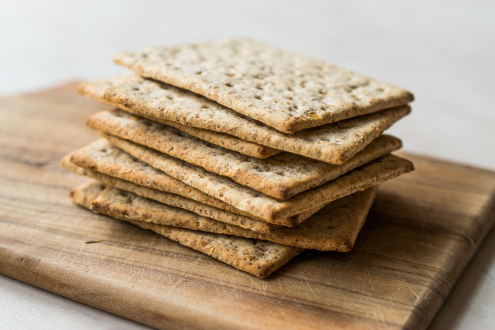 Stack of Honey Flavored Graham Crackers on Wooden Surface.