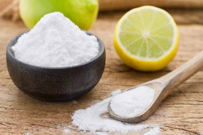 baking soda in a wooden bowl with a wooden spoon, and lemon on a wooden surface