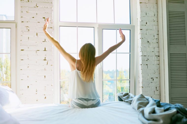 Woman stretching in bed after waking up, back view, entering a day happy and relaxed after good night sleep. Sweet dreams, good morning, new day, weekend, holidays concept