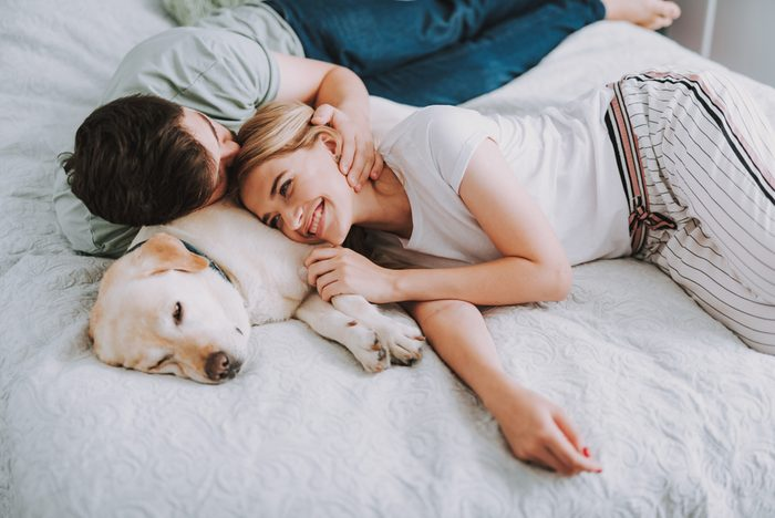 Pleasant young couple having rest in bed while their dog sleeping nearby