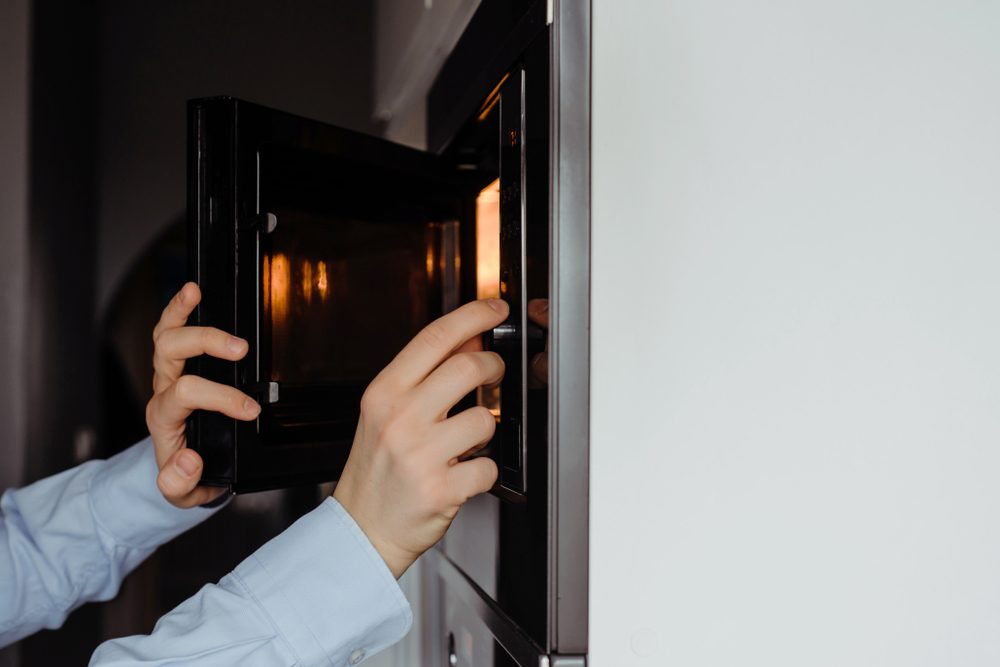 A man dressed in a business shirt puts a dish into the microwave oven.