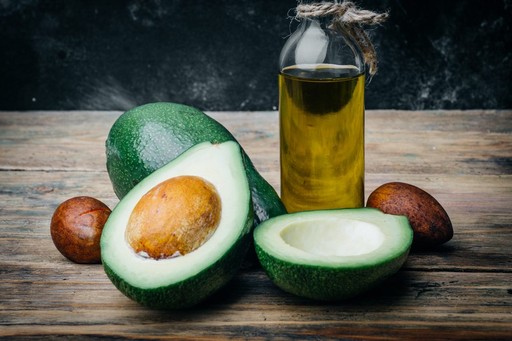 Avocado and avocado oil on a wooden table.