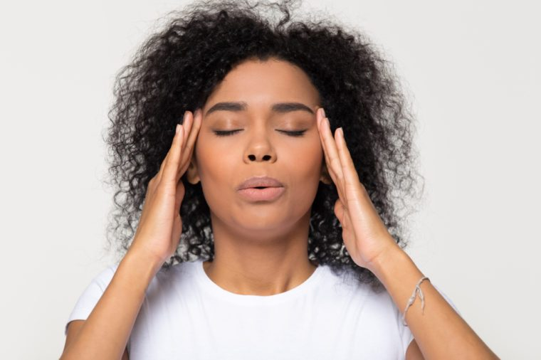Nervous woman trying to take relaxing, calming breaths while massaging her temples.
