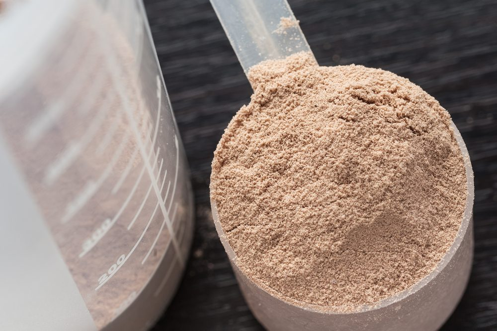 Scoop of chocolate whey isolate protein next to the translucent protein shaker, with focus on the protein inside the scoop