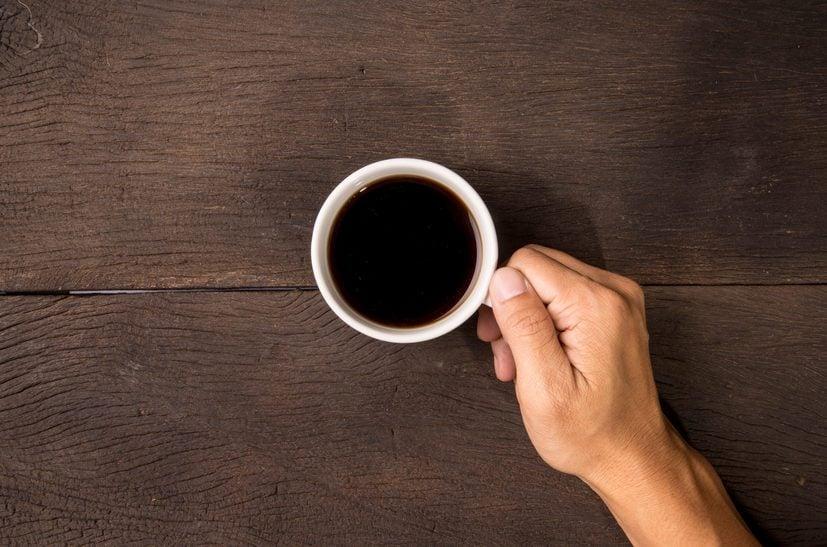 Male hand hold mug of espresso coffee on wood table.