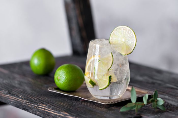 Cold cocktail with lime, lemon, tonic, vodka and ice on vintage shelf.