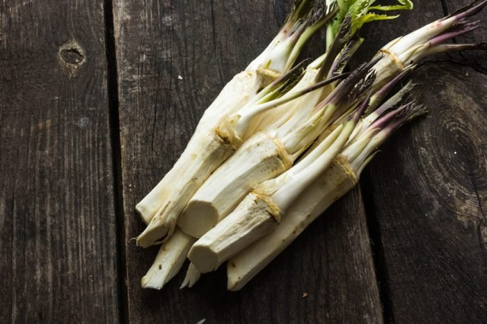 raw horseradish root with leaves on wooden background.