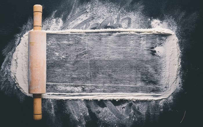 Rolling pin and white flour on a dark background.
