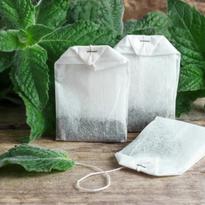 White packages of disposable tea with mint branches on a wooden background