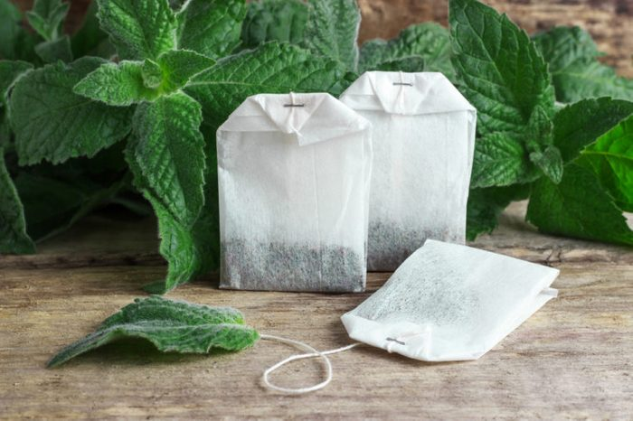 White packages of disposable tea with mint branches on a wooden tabletop.