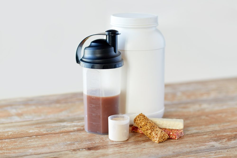 Protein shake bottle and muesli bars on wooden table.