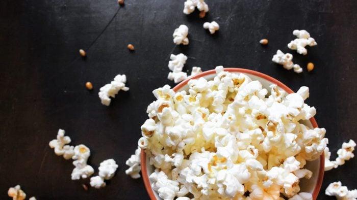 Popcorn in bowl on black background.