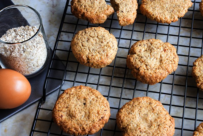 Glutenfree homemade oatmeal cookies on a cooling rack alongside a cup of oats and an egg.
