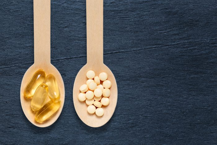 Healthy vitamins and fish oil on spoons against rustic stone background
