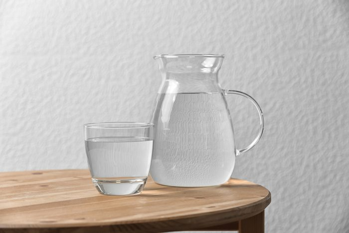 Pitcher and glass with water on table near white wall