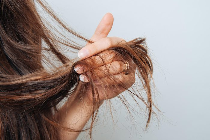 woman holding the ends of her long hair