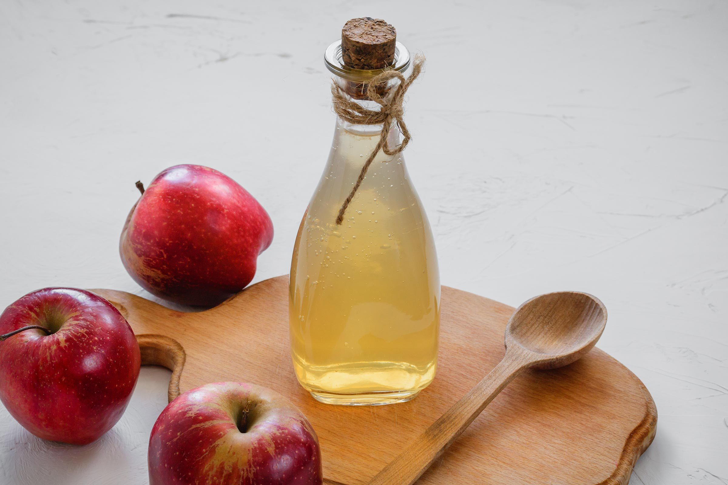 bottle of apple cider vinegar, spoon, and apples