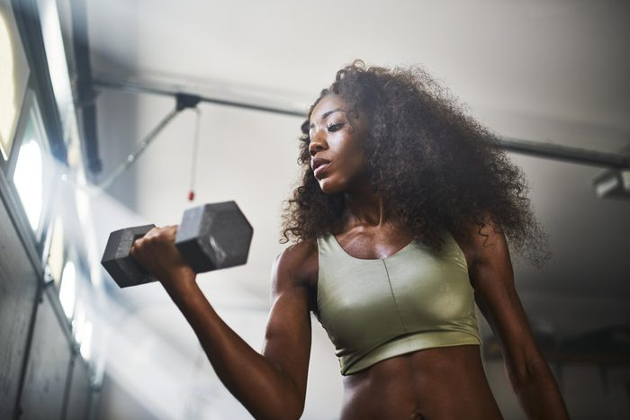 woman doing a bicep curl with weight