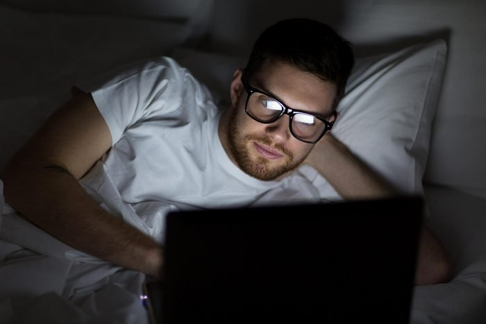 man in bed looking at his laptop at night in a dark room