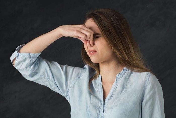 Woman pinching her nose.