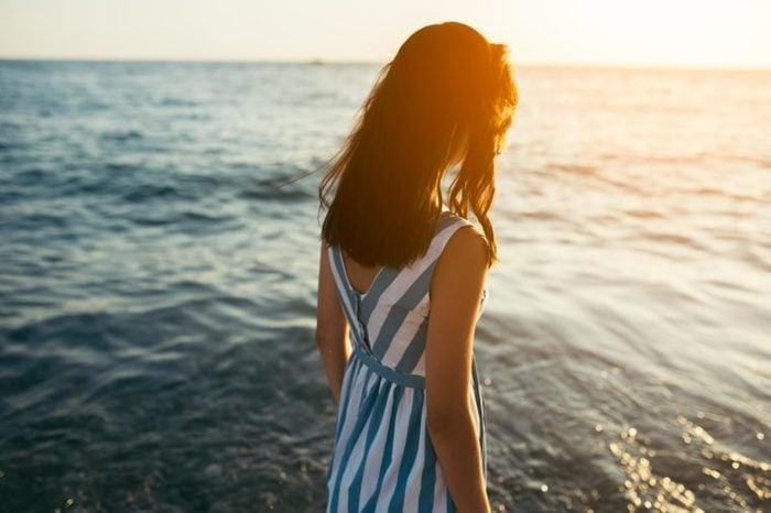 woman sun flare beach water
