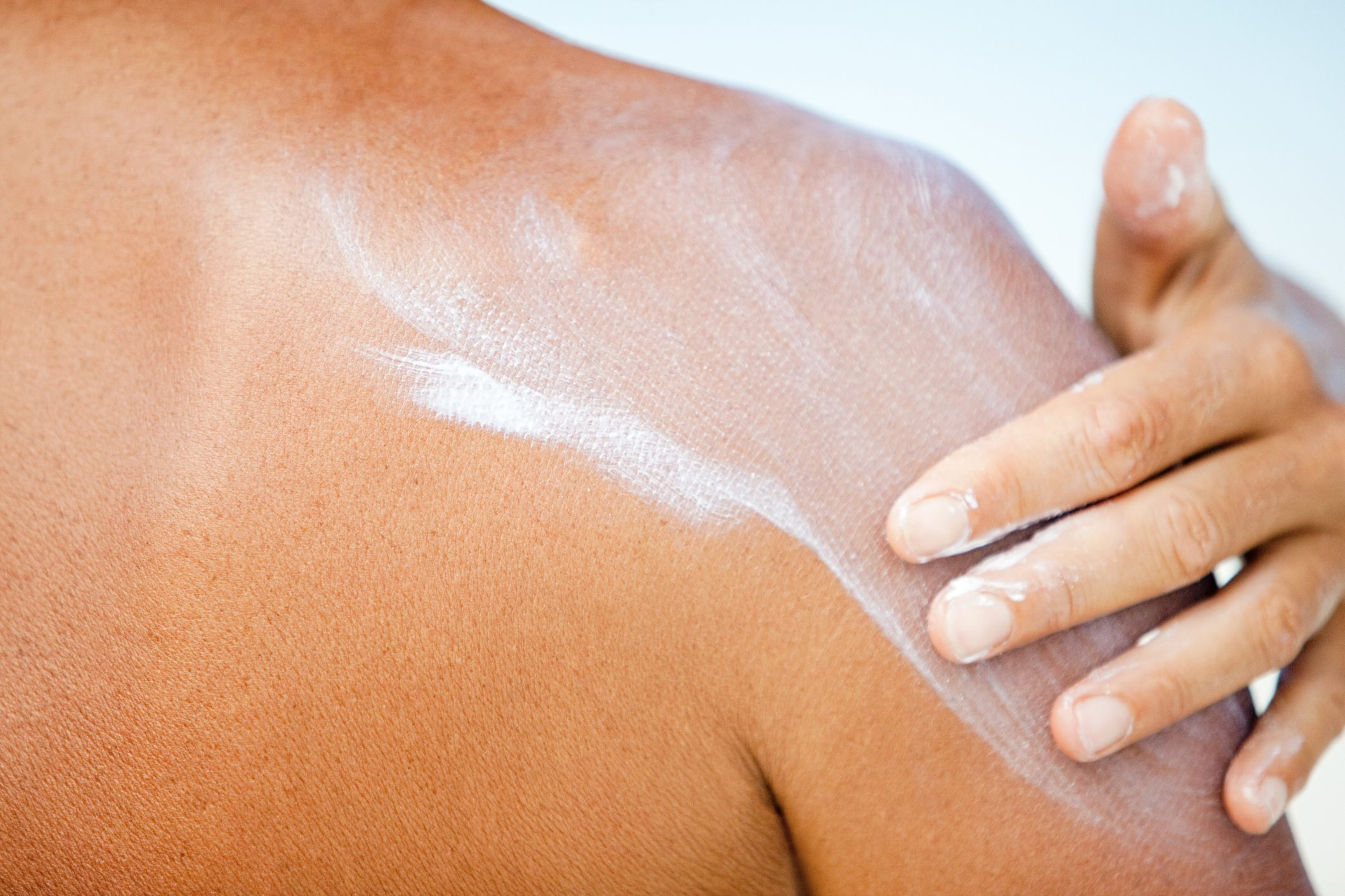 closeup of woman applying sunscreen to shoulder