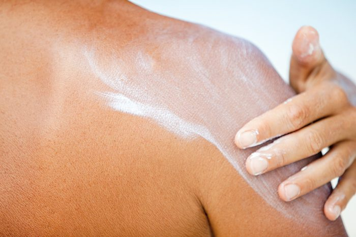 closeup of woman applying sunscreen to shoulder