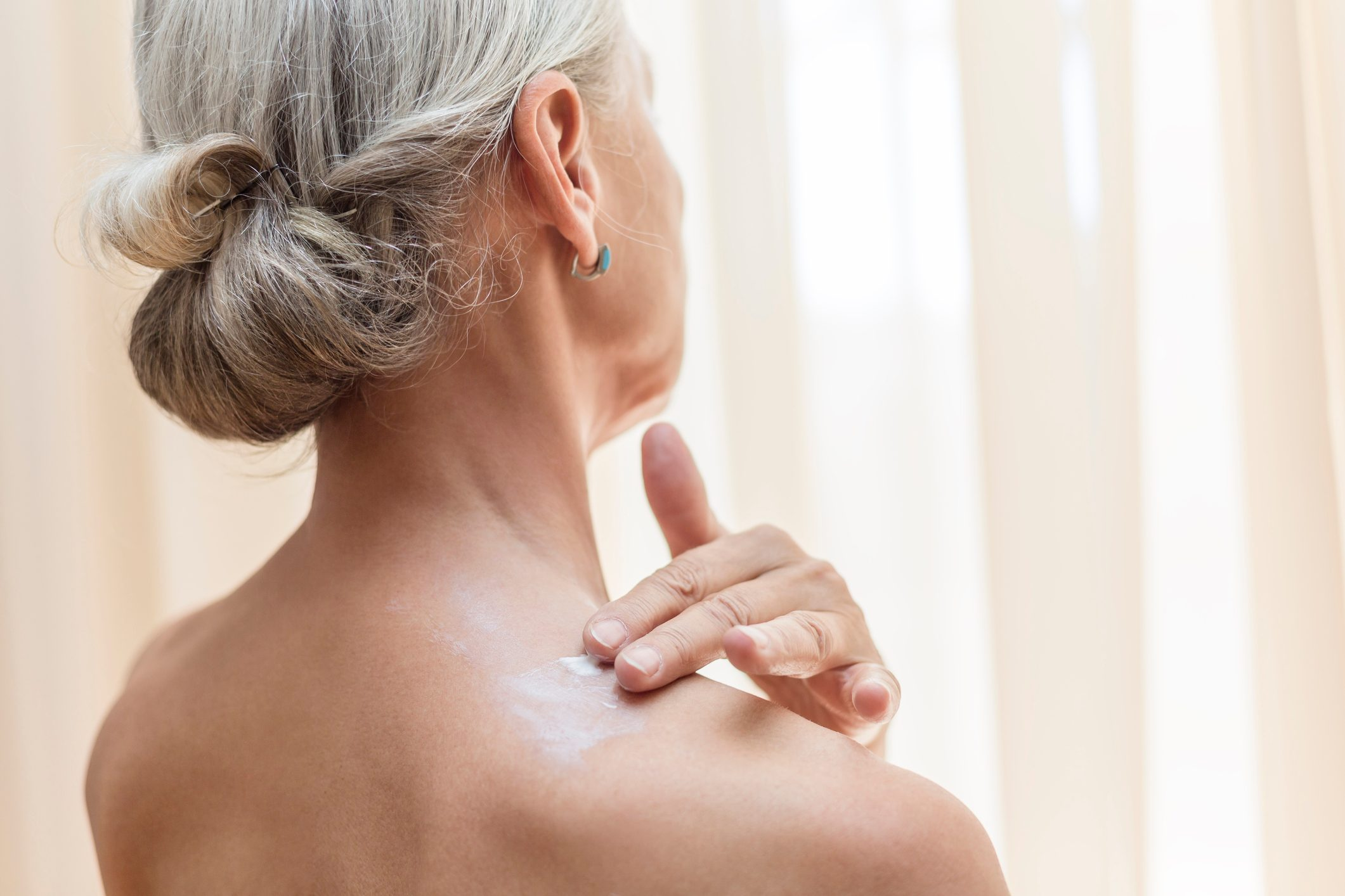 close up of senior woman applying lotion to back