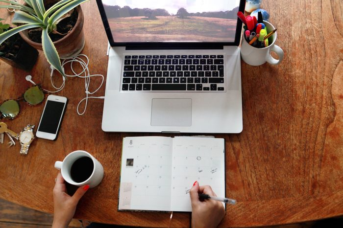 high angle shot of desk with laptop and schedule planner