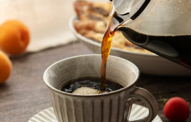 close up of pouring hot coffee into mug
