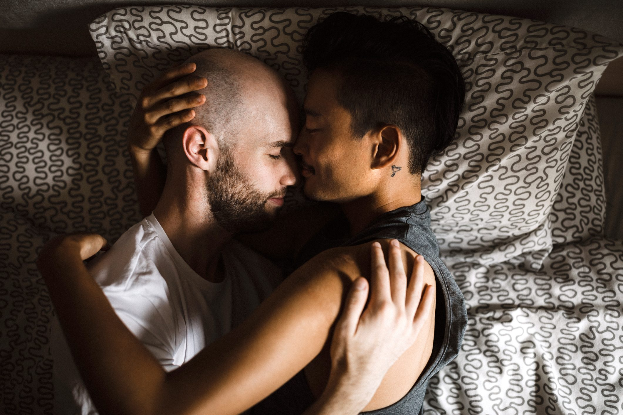 gay couple laying in bed together embracing