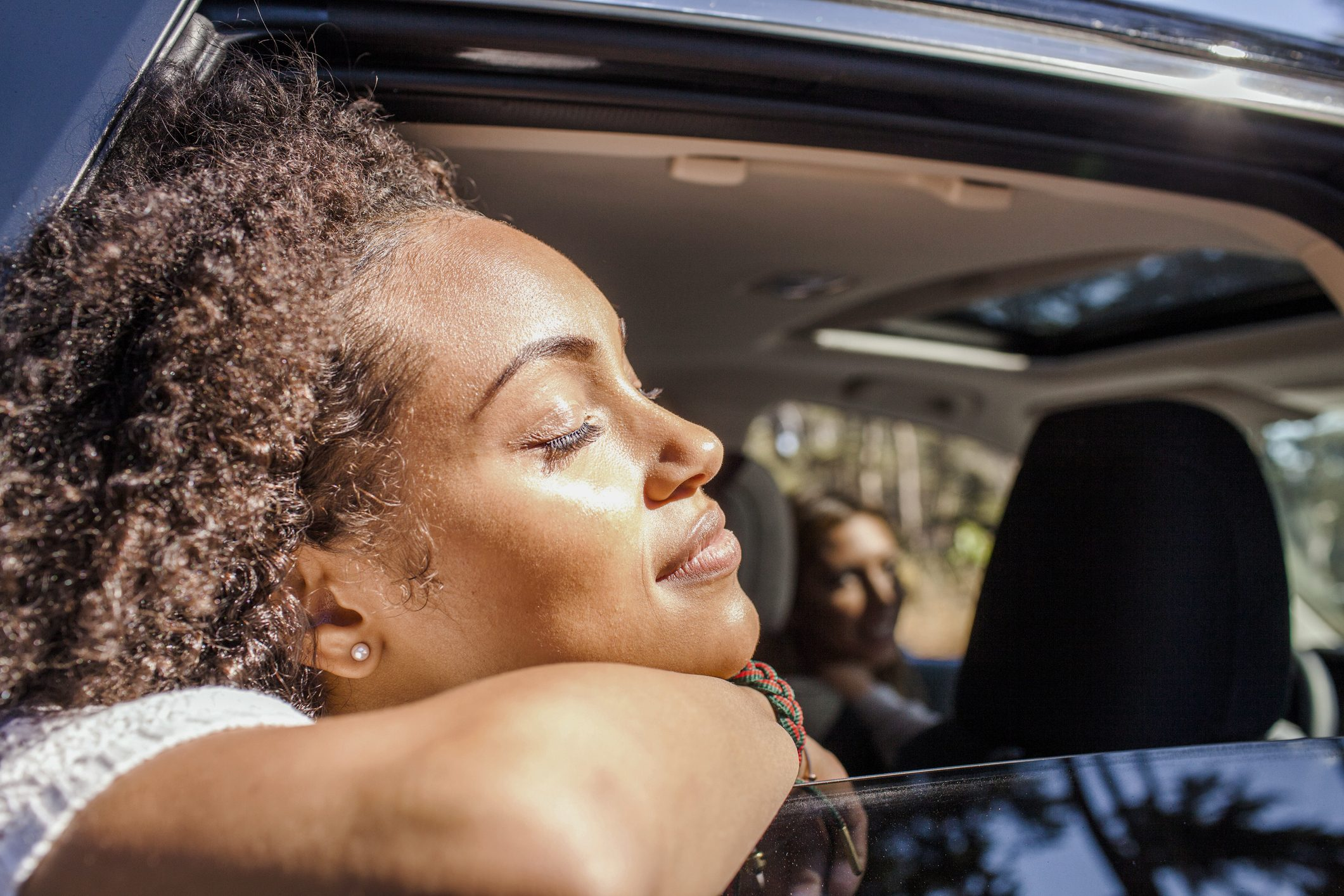 woman with head out of car window soaking up the sunshine