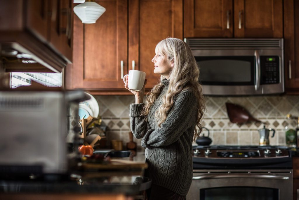 woman drinking morning cup of coffee in kitchen and looking out window