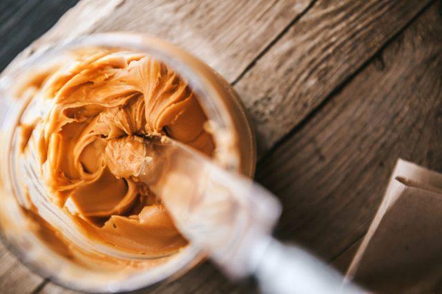 overhead view of knife inside peanut butter jar