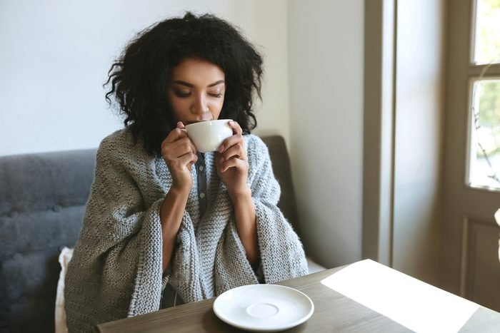Beautiful African American girl drinking coffee in restaurant. Portrait of young lady with dark curly hair dreamily closing her eyes with cup in hands. Nice girl sitting in cafe with cup of coffee
