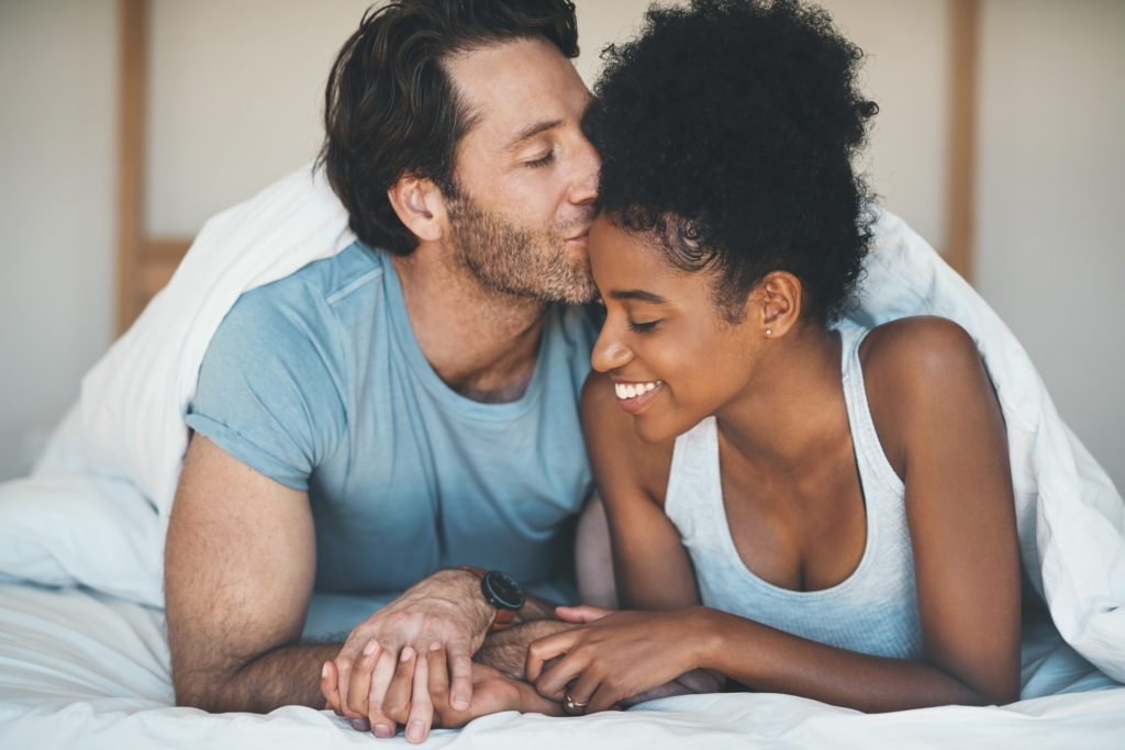 man kissing woman on her forehead in bed