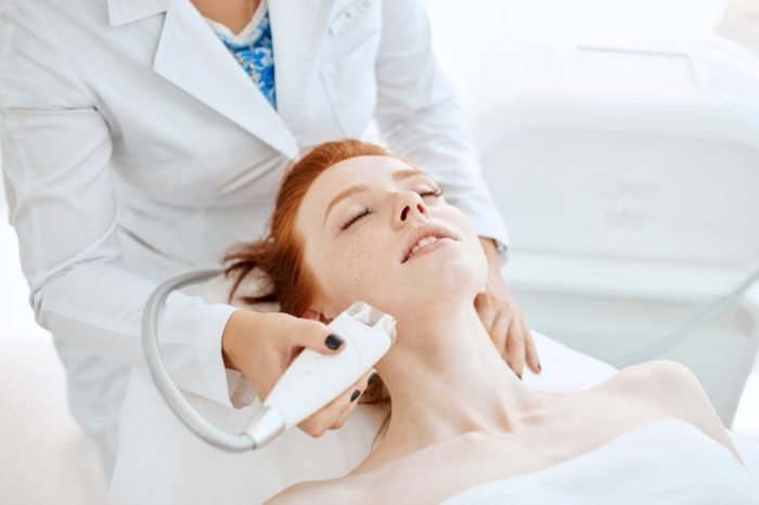 Woman receiving electric facial ultrusound peeling at modern beauty salon. Female patient getting radio frequency lifting on her face.
