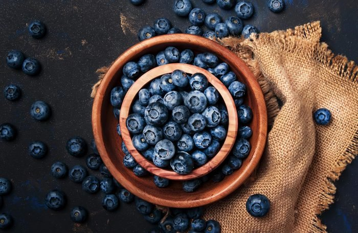 Fresh blueberries in wooden bowl on dark kitchen table background, copy space, top view