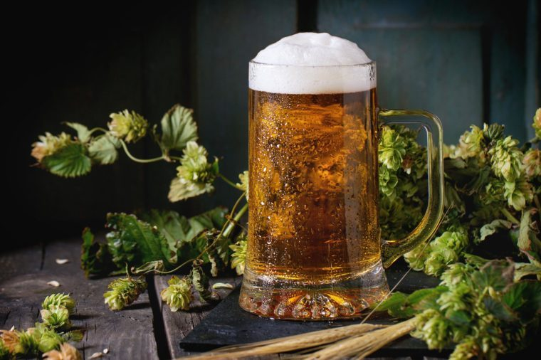Mug of fresh draught lager beer with foam on black slate, served on old wooden table with green hop and ears of barley. Dark rustic style