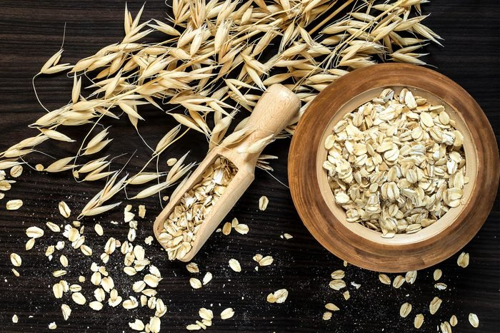 Oat stems and oat flakes in a wooden pot on a dark background. Top view