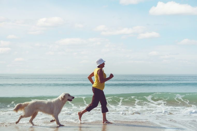 mature woman running beach dog