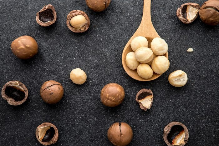 Close up The Macadamia nuts on dark black stone and copy space background , superfood and healthy food concept , overhead or top view shot