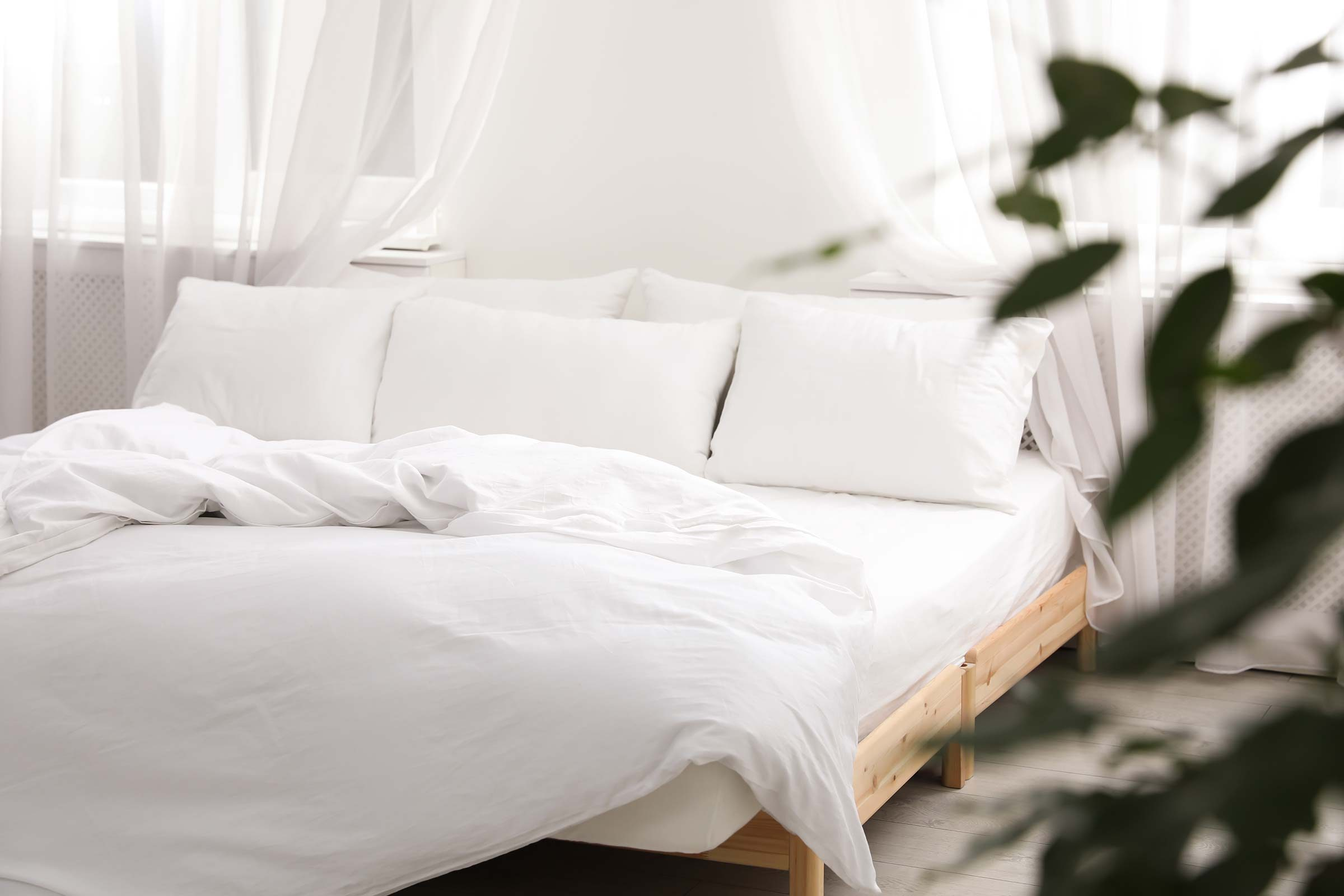 an unmade bed with white linens