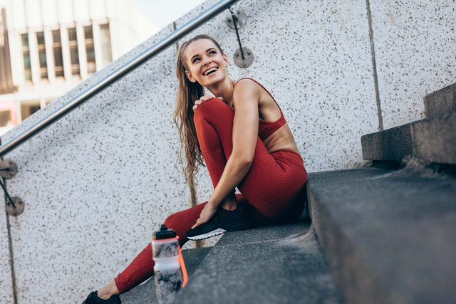woman taking a break from exercise outside on steps