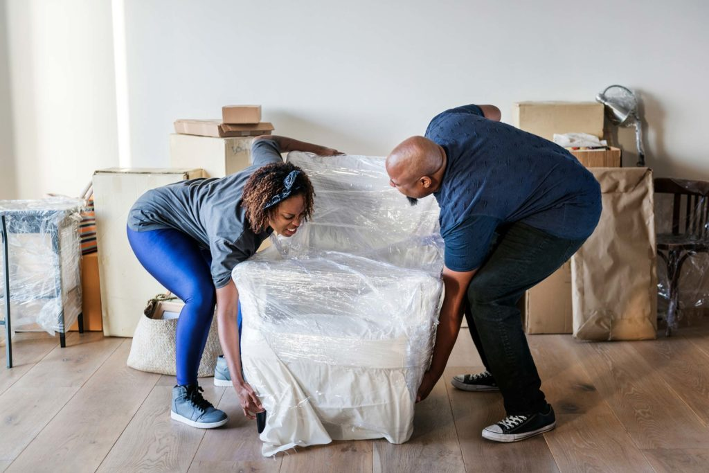 man and woman moving furniture in new home
