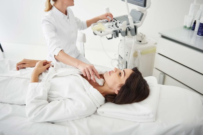 doctor administering a thyroid neck ultrasound