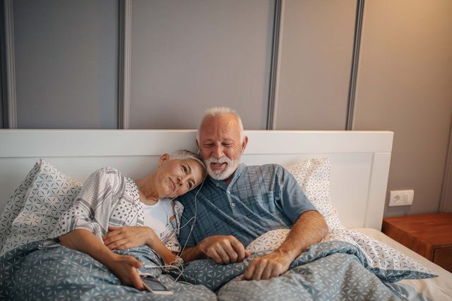 man and woman listening to music in bed